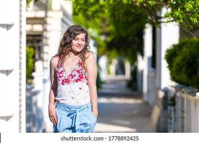 Seaside Florida background of white beach bright residential architecture with young woman girl happy smiling on sunny day wearing pastel clothing