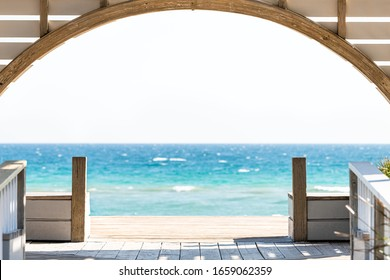 Seaside, Florida framing of wooden pavilion gazebo architecture by beach ocean background view during sunny day - Shutterstock ID 1659062359
