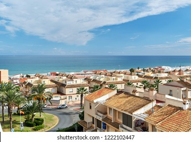 Seaside of Guardamar del Segura city. Coastal residential buildings, houses, architecture of resort town. Rooftops, urban scene. Mediterranean sea and cloudy blue sky in summer. Costa Blanca. Spain
