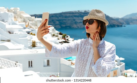 Seaside. Holidays. Technologies. Young woman in summer dress, hat and glasses is taking selfie; sunny weather outside