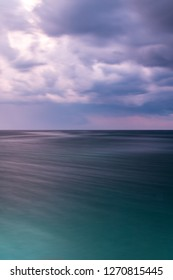 Seaside landscape in gradiant with the sea looking green and the sky looking purple (sunset) with  dramatic clouds