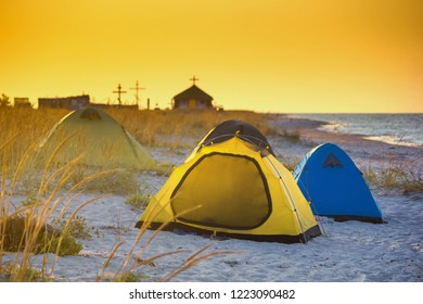Seaside landscape - sunrise on the seashore with tent camp against the background of an Orthodox Skete