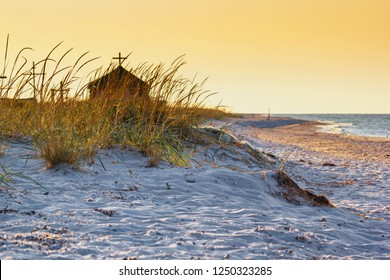 Seaside landscape - sunrise on the seashore with Orthodox Skete against the background of an summer sky