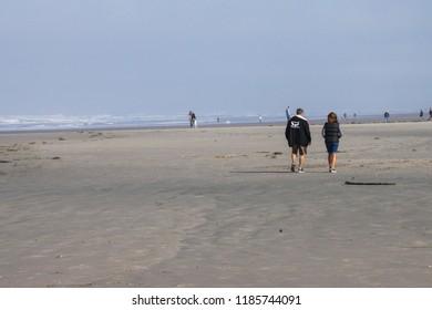 SEASIDE, OREGON - SEP 27. 2014 - Beachcombers walk the sandy beach of Seaside Oregon