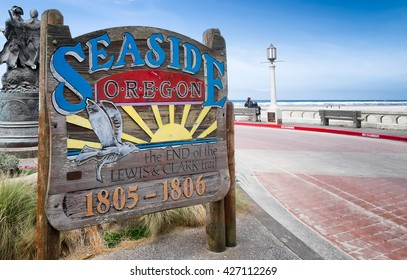 Seaside, Oregon sign commemorating its historic connection to the famous explorers Lewis & Clark, who ended their journey at this spot. A bronze statue of them and the ocean are in the background.