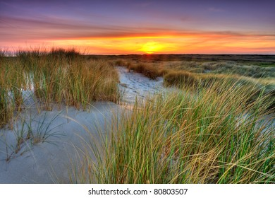 Seaside with sand dunes and colorful sky at sunset