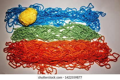 A seaside scene made up of yellow, blue, green and orange wool showing the sky, sun, sea and sand on a white background.
