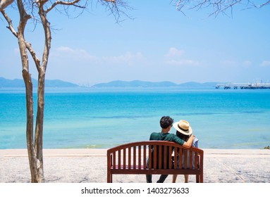 At seaside in summer , happy young couple in love relaxing on beach vacation enjoying ocean view together sitting on wooden chair , blue sea and blue sky background .