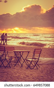 Seaside table and chairs outdoor on sand beach. Golden sunset and walking people in the background. Summer vacation on resort. Rural scene.