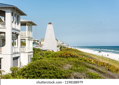 Seaside, USA - April 25, 2018: Wooden pavilions by beach ocean with coastline, gazebo in Florida, sand, architecture, view during sunny day, flock of pelican birds flying