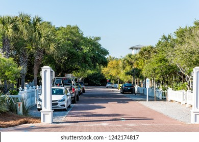Seaside, USA - April 25, 2018: Wooden houses community parking cars parked in lot by beach ocean, nobody on vacation in Florida view during sunny day