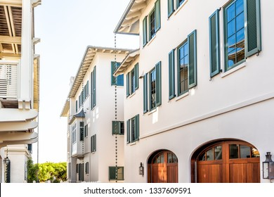Seaside, USA - April 25, 2018: Wooden houses community parking garage townhomes by beach ocean, nobody on vacation in Florida during sunny day
