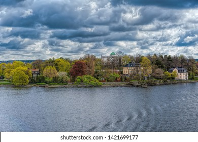 Seaside view of Djurgarden island with waterfront villas and colorful blooming trees at spring sunny morning. Stockholm, Sweden.