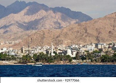 Seaside view of the jordan city of Aqaba at the Red Sea. Deep blue sea, white buildings, green trees and majestic hills.