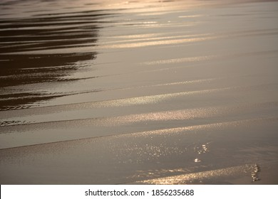 Seaside view with light effects and reflections in the water, wet sand with sparkles...