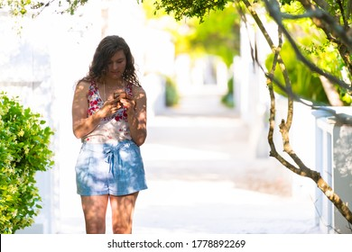 Seaside white beach bright residential architecture with young woman girl texting using phone in Florida during sunny day wearing pastel clothing