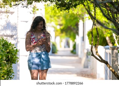 Seaside white beach residential architecture with young woman girl texting using phone in Florida during sunny day wearing pastel clothing