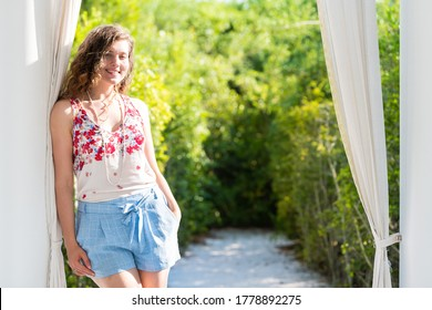 Seaside white column architecture with happy young woman girl standing smiling in sunny sunlight in Florida with green foliage trees in blurry background