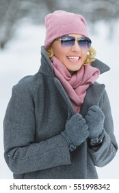 season, christmas, holidays and people concept - smiling young woman in winter clothes outdoor