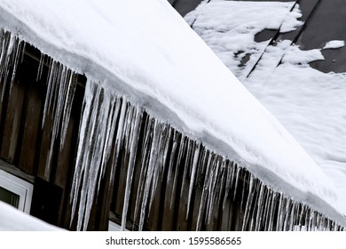 Season. Icicles on the roof of the house. housing and winter concept .