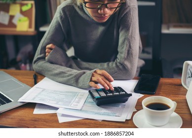 Season to pay Tax and Budget planning concept. Business woman calculating annual tax and using mobile phone. Calendar 2021 and personal income tax form placed on home office desk.
