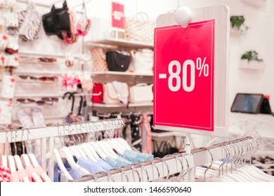 Season sale, black friday and shopping concept. Red stand 80 percent discount price in shop. Clothes hangers on background.