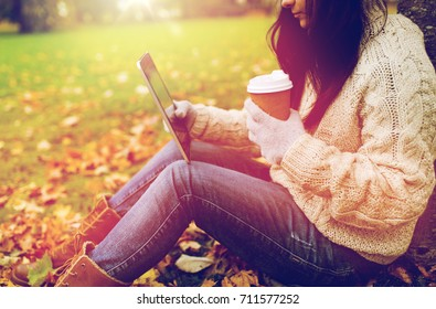 season, technology and people concept - young woman with tablet pc and coffee cup sitting on grass in autumn park