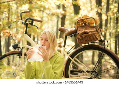 Seasonal allergy. Woman with handkerchief sneezing because of allergy. Blonde with allergic reaction relax forest. Girl with bicycle in nature. Woman with bicycle autumn forest suffers from allergy.