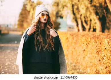 Seasonal autumn fashion. Modern young woman wearing fashionable warm clothes posing in the autumn park.