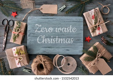Seasonal background from above. Hand crafted gifts on rustic wooden table with Christmas decorations. Flat lay, top view, filtered image. Tag mockup, copy space on wood in the center and paper tags.