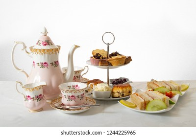 Seasonal cream tea, a lovely english tradition, pretty china teapot and cups with cake, scones and sandwiches, on a 2 tier plate.