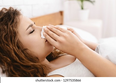 Seasonal flu. Sick young woman has runny nose at home, blowing her nose into paper napkin lying in bed, copy space