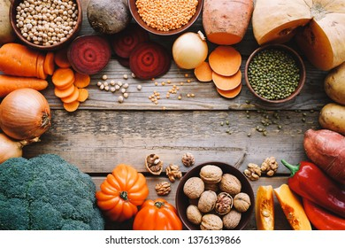 Seasonal food on wooden table. Autumn farm vegetables and legumes