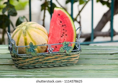 Seasonal fresh fruits, watermelon and rockmelon in basket on garden table