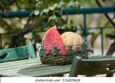 Seasonal fresh fruits, watermelon and rockmelon in basket on garden table
