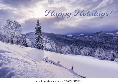 Seasonal greeting card with beautiful winter landscape. Carpathian mountains are covered by mixed forest and heavy fresh snow. Sun is shining through gap in clouds. Happy Holidays sign.