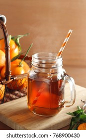 Seasonal and holidays concept. Winter hot tea in a vintage glass with tangerines on a wooden background. Selective focus