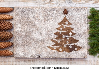 Seasonal and holidays decorations with copy space - christmas tree drawn in flour with pine branches and cones