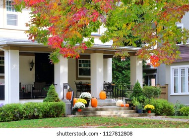 Seasonal house outdoor decoration. Main entrance stair and porch of the stylish house decorated for autumn holidays season, branches of the colorful tree on a foreground. Fall background.