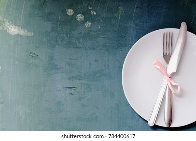 Seasonal old blue wooden table with white  dish and cutlery.