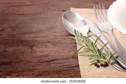 Seasonal old brown wooden table with cutlery and spices.