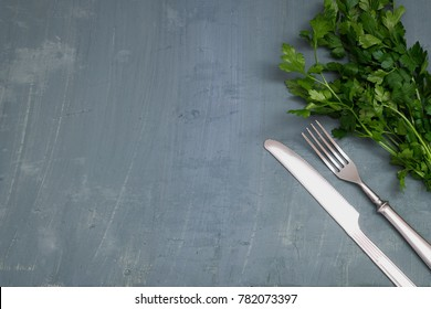 Seasonal old table with cutlery and fresh green parsley.