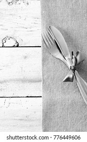 Seasonal old wooden table with cutlery. Black and white photo.