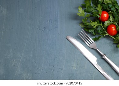 Seasonal old wooden table with cutlery, green parsley and tomato.