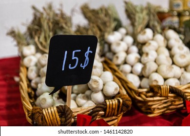 Seasonal products sold at Xmas market. A close up view of a small price sign showing fifteen dollars for strings of garlic in wicker baskets during a local Christmas craft fair, with copy space.