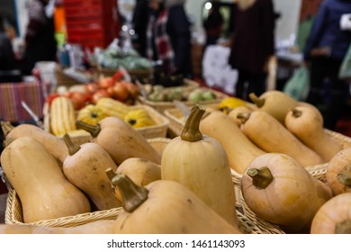 Seasonal products sold at Xmas market. A close up view of winter squashes displayed in wicker baskets during a Christmas fair for local farmers, blurred people are seen behind with copy-space.