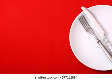 Seasonal red table with white dish and silver cutlery.