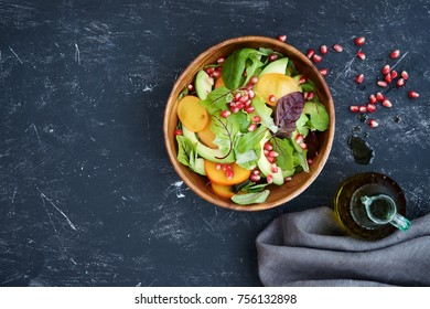 Seasonal salad. Persimmon, avocado, pomegranate and different lettuce leaves in wooden bowl