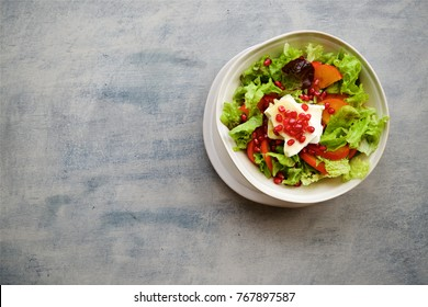 Seasonal salad with persimmon, pomegranate and dressing from honey and mustard. Wooden background, top view