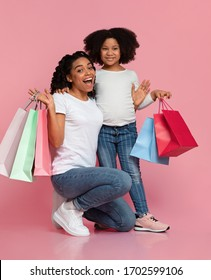 Seasonal Sale. Excited Black Mom And Daughter Standing With A Lot Of Paper Shopping Bags On Pink Background In Studio, Free Space